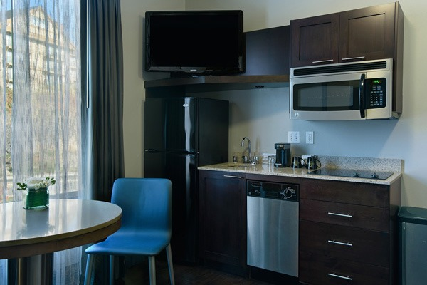 Our Extended Stay King Suite. This fabulous suite is furnished with one king bed, a full bathroom, separate room with twin sofa sleeper, bistro table, and two flat-screen TVs.